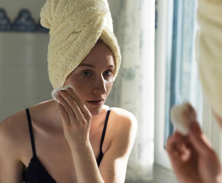 Femme utilisant des produits de soins de la peau