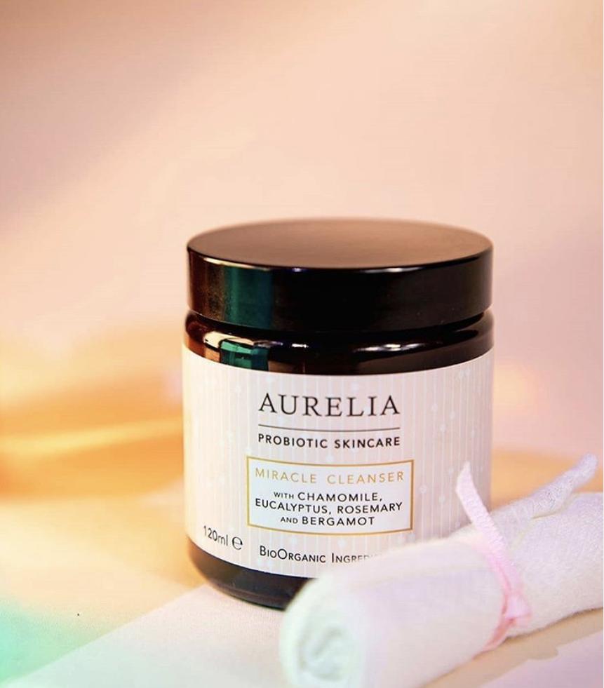 Des nuances de lumière arc-en-ciel entourent une bouteille de nettoyant miracle Aurelia, indispensable pour ces tendances beauté estivales. Une mousseline de bambou rose se trouve à côté de la bouteille.