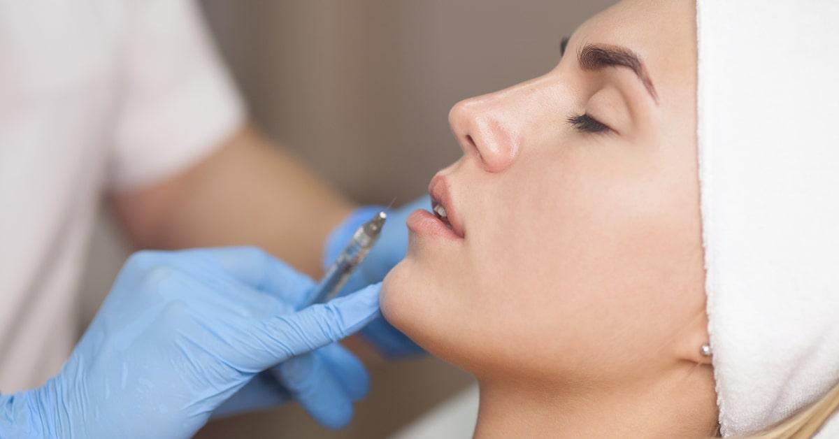 Dermal Filler Injectables - Consultant sur le point d'injecter un produit de comblement dermique dans les lèvres des filles