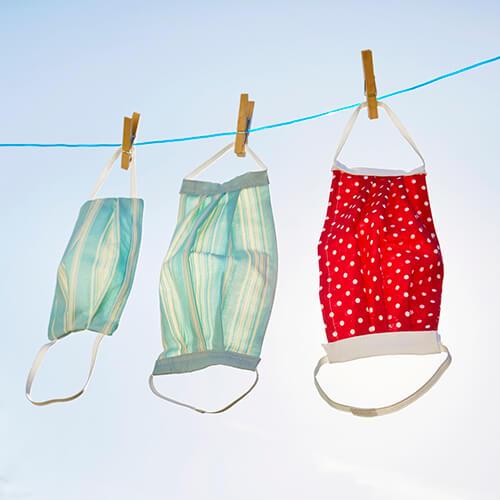 masques réutilisables accrochés à une corde à linge