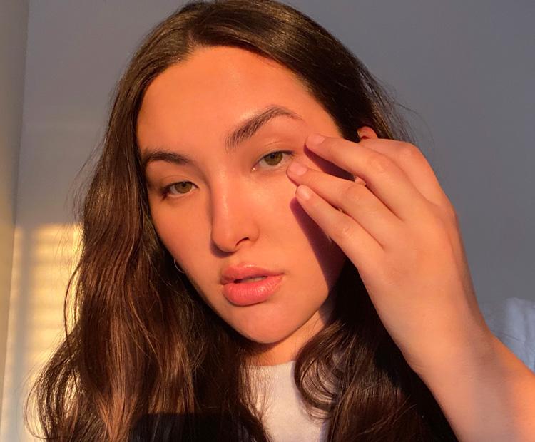 femme touchant son visage