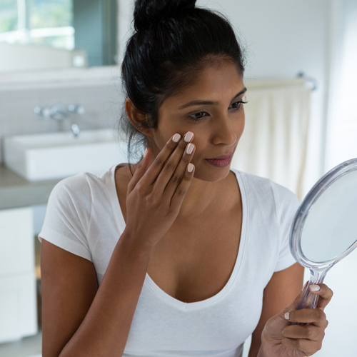 Femme latino examinant sa peau