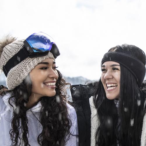 deux femmes souriant sur la piste de ski