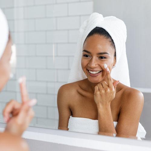 femme mettant sur la crème pour le visage
