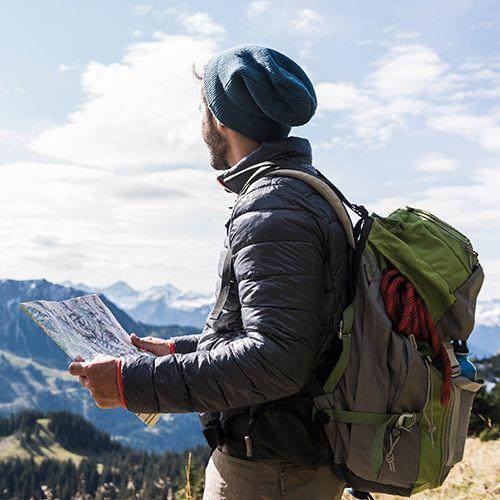 Homme avec chapeau à l'extérieur tenant une carte et regardant les montagnes