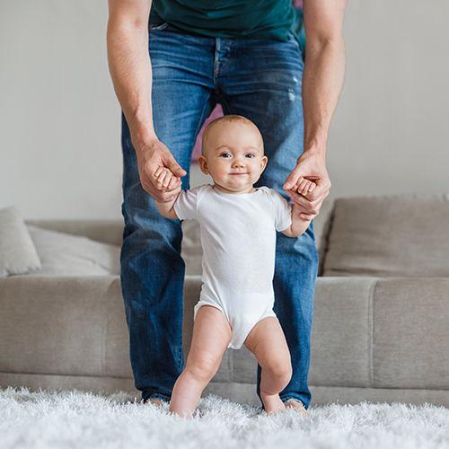 Bébé marche avec l'aide de papa