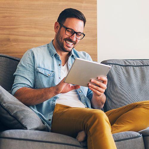 Homme, à, lunettes, sur, divan, utilisation, tablette, et, sourire