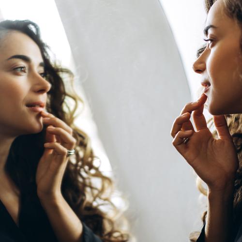 femme vérifiant sa peau dans le miroir
